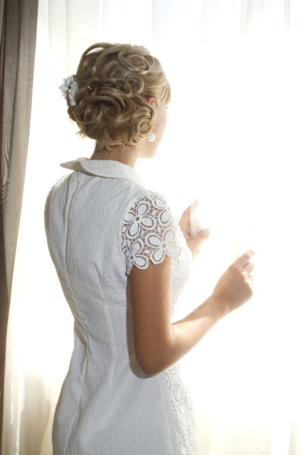 Bruid door het venster stock foto