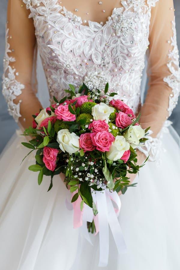 Bruid in een kantkleding die een huwelijksboeket van witte en roze rozen houden stock foto