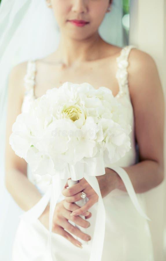 bruid in een kleding die zich in een groene tuin bevinden en een huwelijksboeket van bloem houden stock foto's