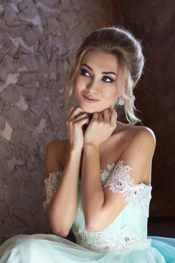 Bruid in een mooie turkooise kleding in afwachting van het huwelijk Blonde in groene het overzees van de kantkleding Gelukkige br royalty-vrije stock afbeelding