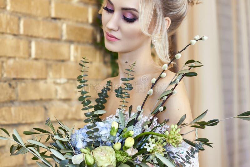 Bruid in een mooie turkooise kleding in afwachting van huwelijk Blonde in het overzees van de kantkleding groen met een boeket Ge stock afbeelding