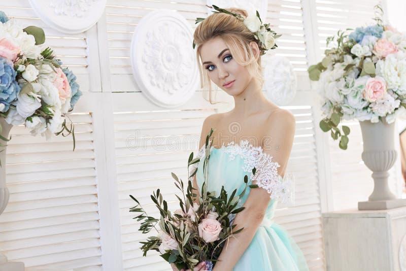 Bruid in een mooie turkooise kleding in afwachting van huwelijk Blonde in het overzees van de kantkleding groen met een boeket Ge stock foto