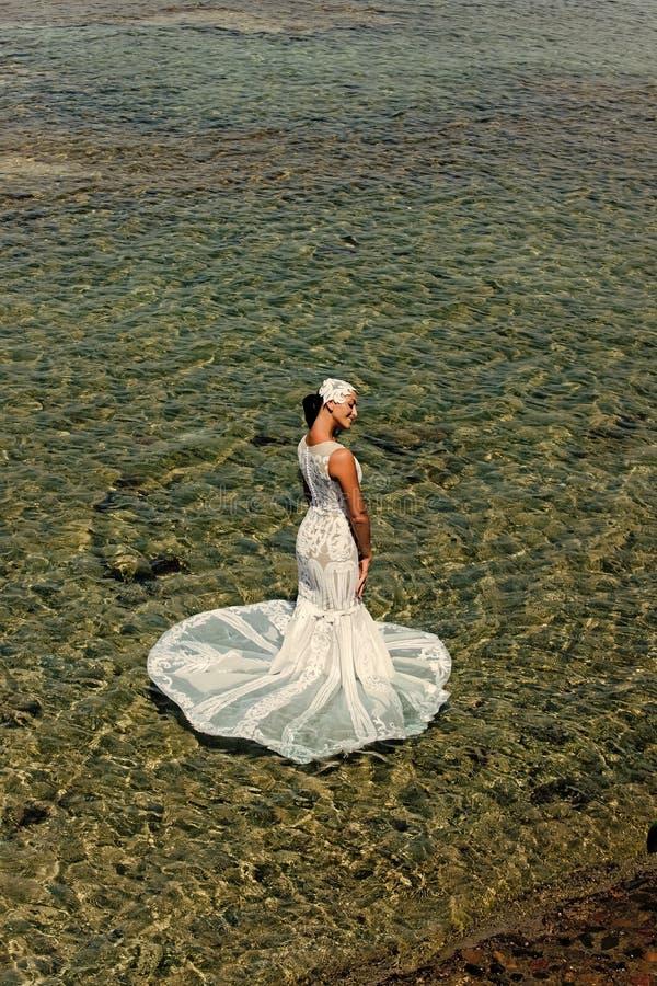 Bruid in een natte huwelijkskleding Brunette in Witte huwelijksKleding stock foto