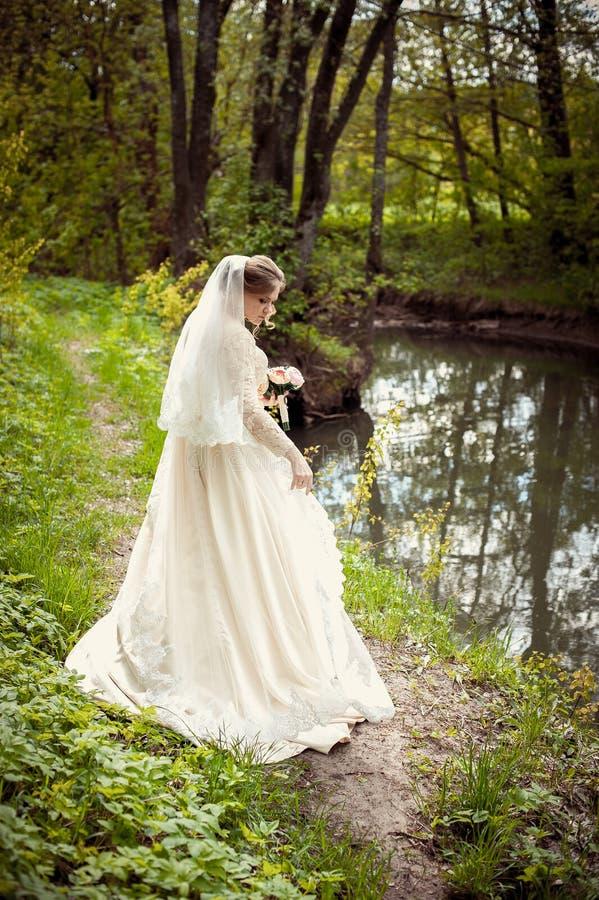 Bruid in een witte kleding op de achtergrond van aard Huwelijksfotografie royalty-vrije stock foto