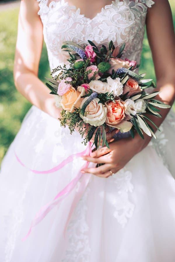 Bruid in een witte kleding op een zonnige dag, die in handen een mooi huwelijksboeket houden stock afbeeldingen