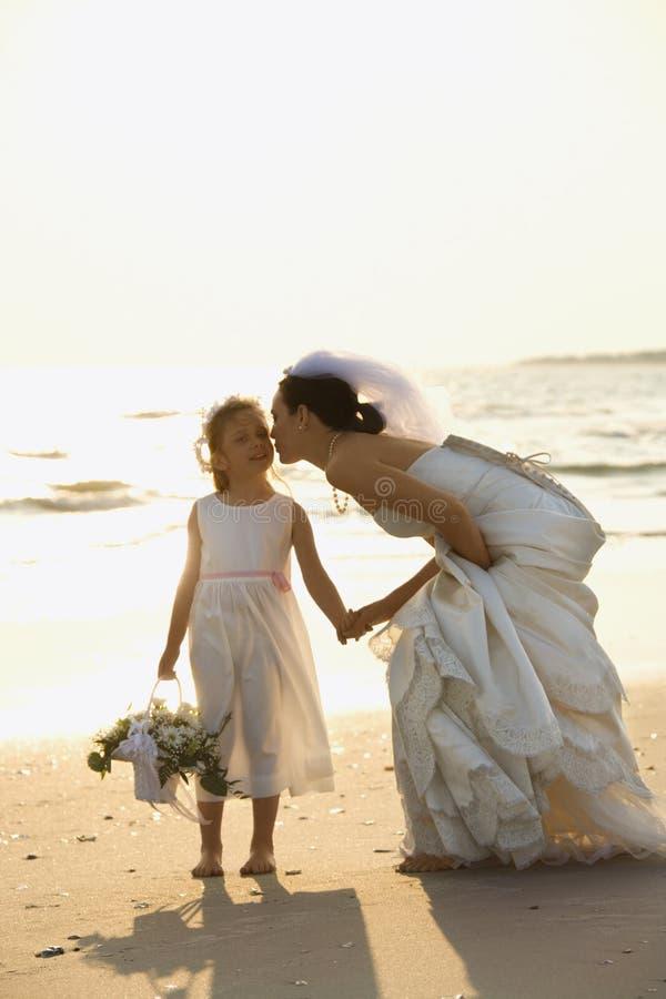 Bruid en bloemmeisje op strand.