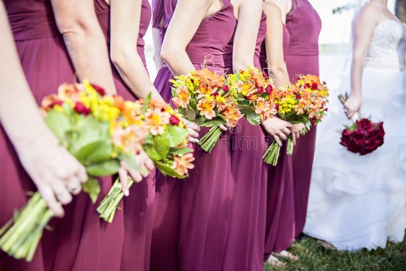 Bruid en Bridemaids-holdingsboeketten stock afbeelding