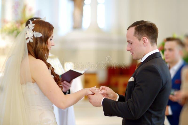 Bruid en bruidegom bij de kerk tijdens een huwelijk stock afbeeldingen