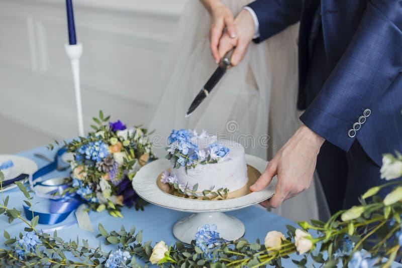 Bruid en bruidegom bij huwelijk die de cake snijden stock afbeelding