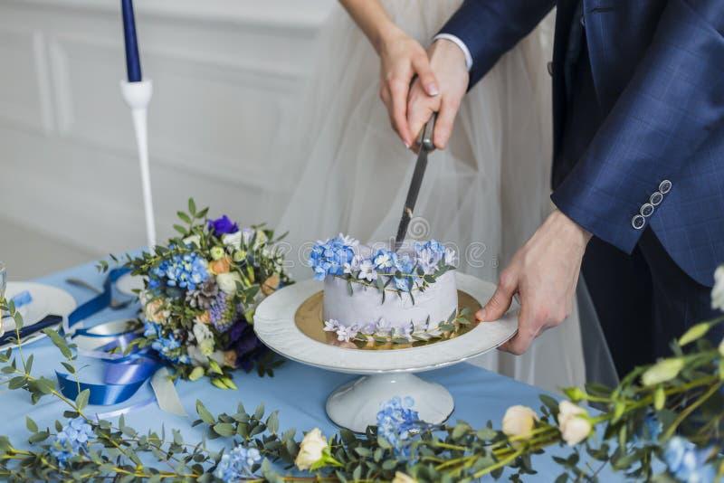 Bruid en bruidegom bij huwelijk die de cake snijden royalty-vrije stock foto's