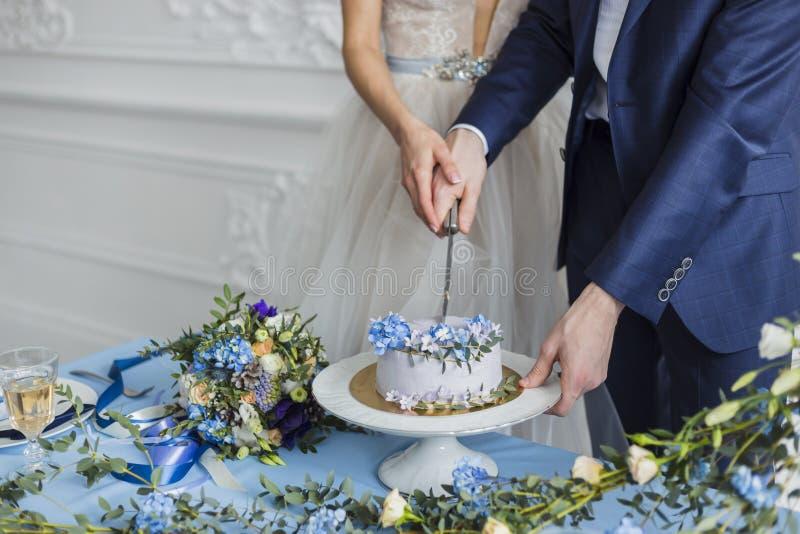 Bruid en bruidegom bij huwelijk die de cake snijden stock foto