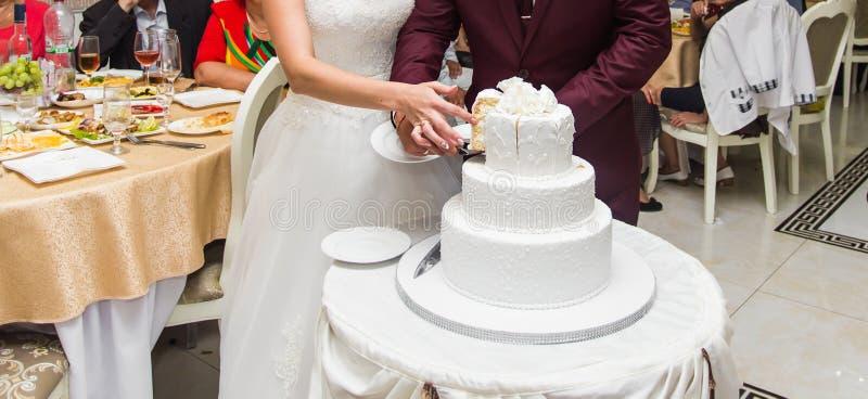 Bruid en Bruidegom bij Huwelijksontvangst die de Cake snijden stock fotografie
