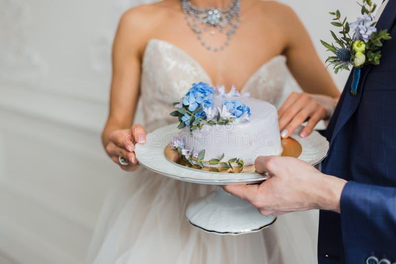 Bruid en bruidegom de cake van het greephuwelijk stock fotografie