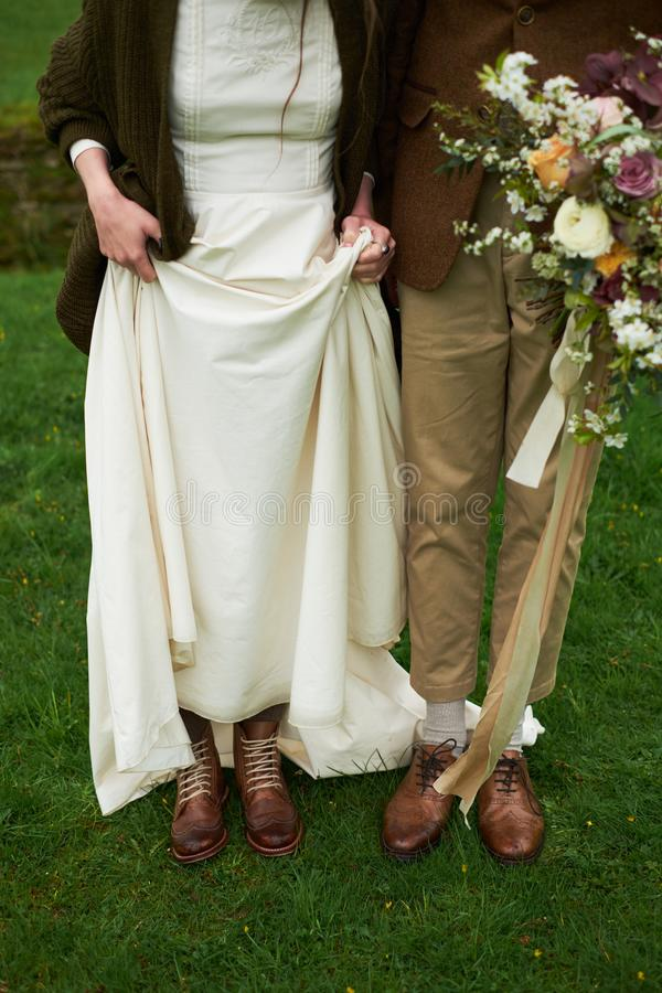Bruid en bruidegom in de herfst bruine schoenen op het gras, die benen, huwelijksconcept tonen stock foto