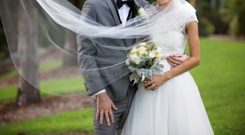 Bruid en Bruidegom de Sluier van Pose With Flowing royalty-vrije stock foto's