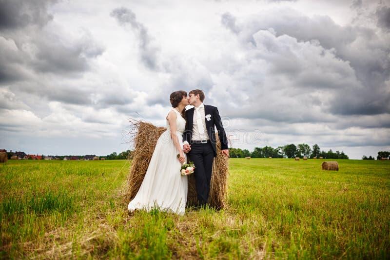 Bruid en bruidegom dichtbij hooi royalty-vrije stock fotografie