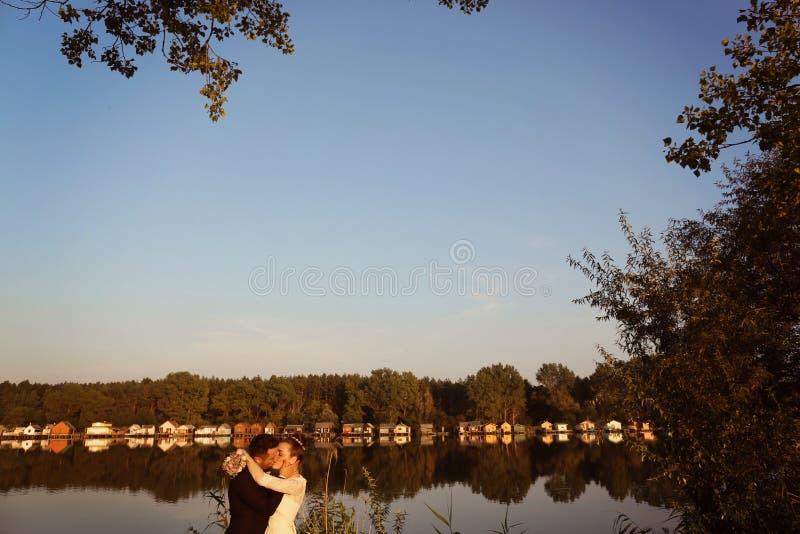 Bruid en bruidegom dichtbij meer stock foto's