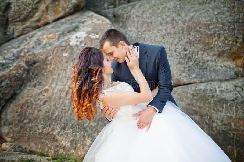 Bruid en bruidegom die bij huwelijksdag in openlucht op de lenteaard koesteren royalty-vrije stock fotografie