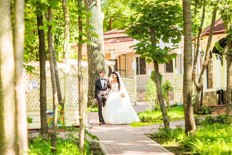 Bruid en Bruidegom die bij huwelijksdag in openlucht op de lenteaard lopen Bruids paar, Gelukkige Jonggehuwdevrouw en man het omh royalty-vrije stock foto