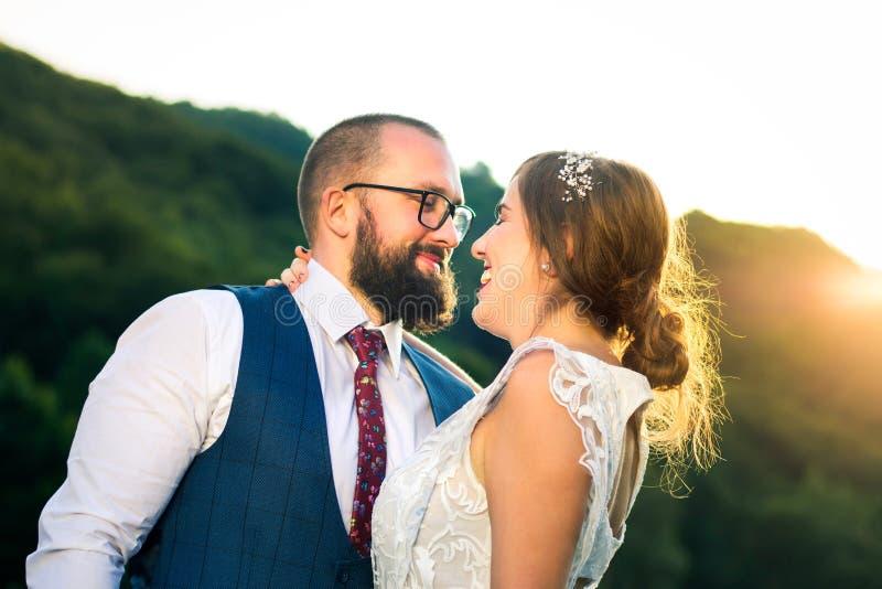 Bruid en bruidegom die bij romantische zonsondergang koesteren royalty-vrije stock afbeeldingen