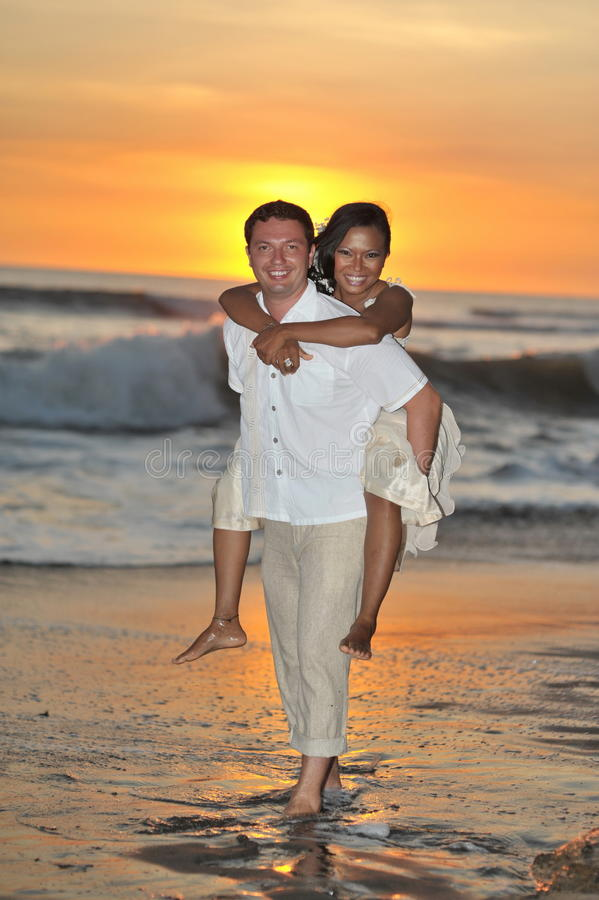 Bruid en bruidegom die blootvoets op strand lopen royalty-vrije stock fotografie