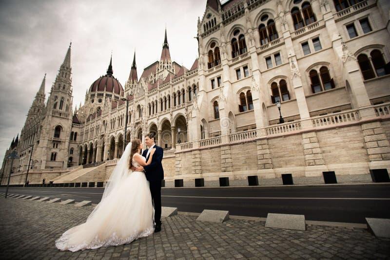 Bruid en bruidegom die in de oude stadsstraat koesteren De gangen van het huwelijkspaar in Boedapest dichtbij het Parlement Huis royalty-vrije stock foto's