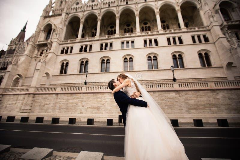 Bruid en bruidegom die in de oude stadsstraat koesteren De gangen van het huwelijkspaar in Boedapest dichtbij het Parlement Huis royalty-vrije stock afbeelding