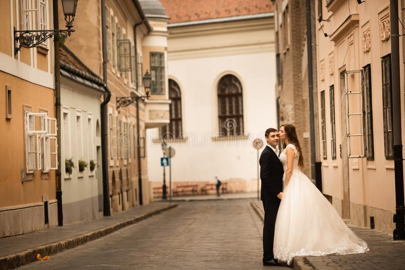 Bruid en bruidegom die in de oude stadsstraat koesteren Wedingspaar in liefde Het wieden in Boedapest stock foto's