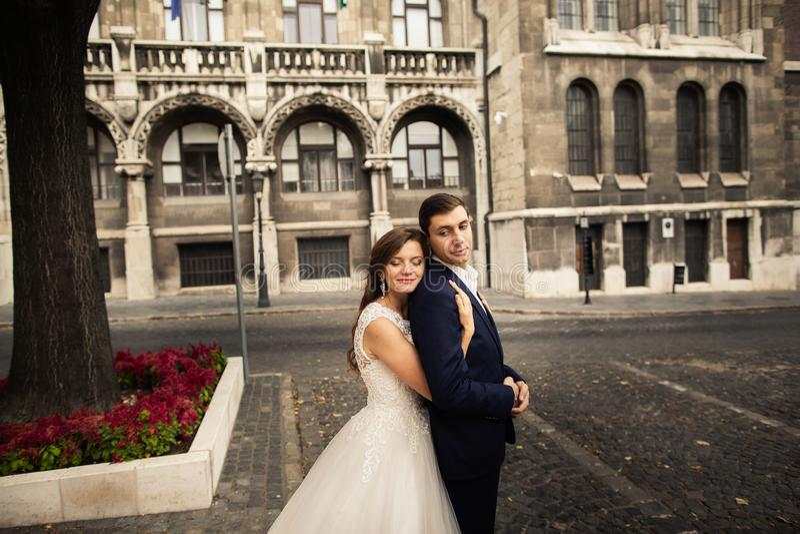 Bruid en bruidegom die in de oude stadsstraat koesteren Wedingspaar in liefde Het wieden in Boedapest stock afbeeldingen
