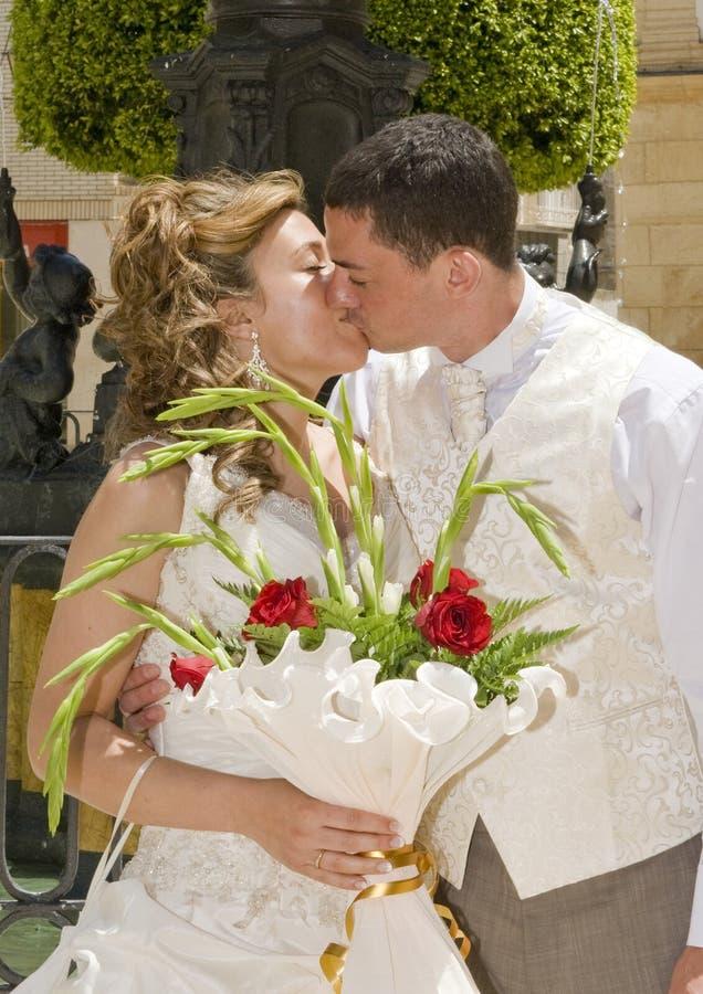 Bruid en Bruidegom die een kus ruilen royalty-vrije stock afbeelding