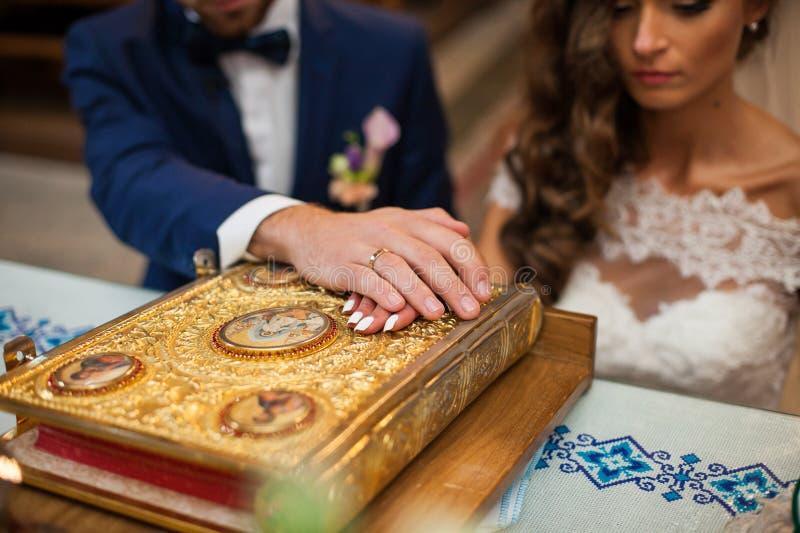 Bruid en bruidegom die geloften in kerk op oude gouden bijbel doen stock afbeeldingen