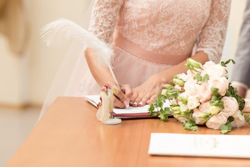 Bruid en bruidegom die het huwelijkscontract na de huwelijksceremonie ondertekenen royalty-vrije stock foto's