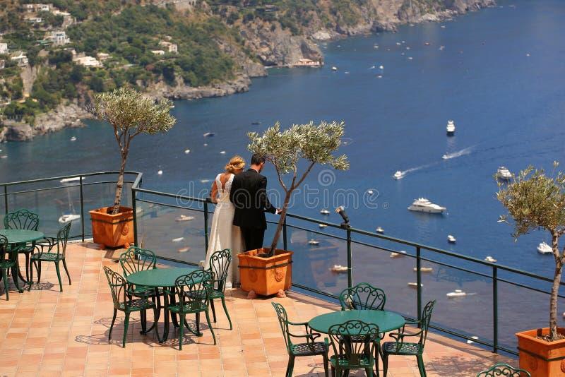 Bruid en bruidegom die het overzees bekijken royalty-vrije stock afbeelding