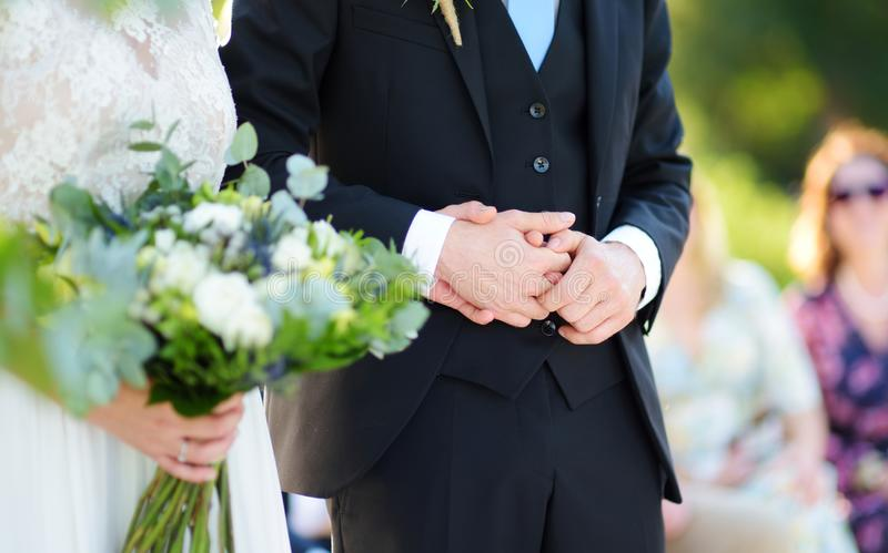 Bruid en bruidegom die hun handen in openlucht houden tijdens mooie huwelijksceremonie op de zomerdag royalty-vrije stock afbeelding