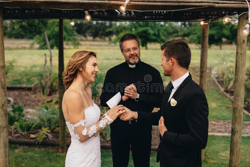 Bruid en bruidegom die huwelijksgeloften op huwelijksceremonie ruilen stock afbeelding