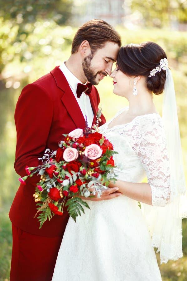 Bruid en bruidegom die, huwelijkspaar, donkerrood de stijlontwerp van kleurenmarsala omhelzen Kostuum met kastanjebruine vlinderd royalty-vrije stock foto