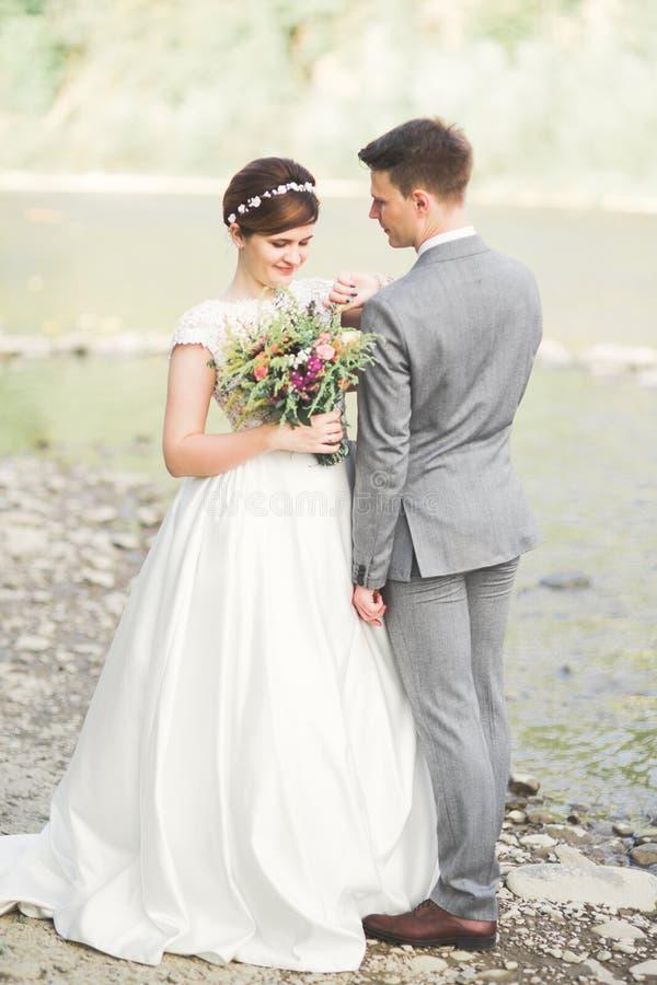 Bruid en bruidegom die mooi huwelijksboeket houden Het stellen dichtbij rivier royalty-vrije stock afbeeldingen