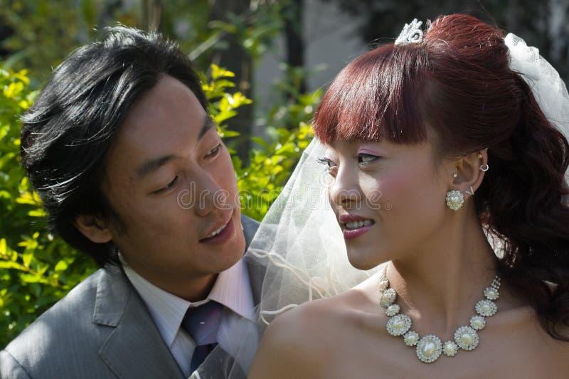 Bruid en bruidegom die op elkaar letten stock fotografie