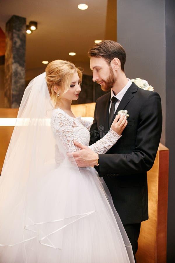 Bruid en bruidegom die en op hun huwelijksdag koesteren kussen Creati stock afbeeldingen