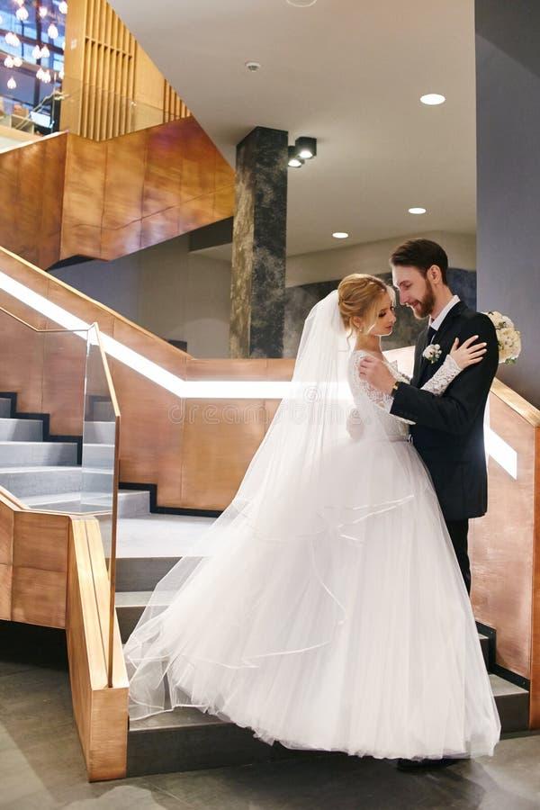 Bruid en bruidegom die en op hun huwelijksdag koesteren kussen Creati stock fotografie