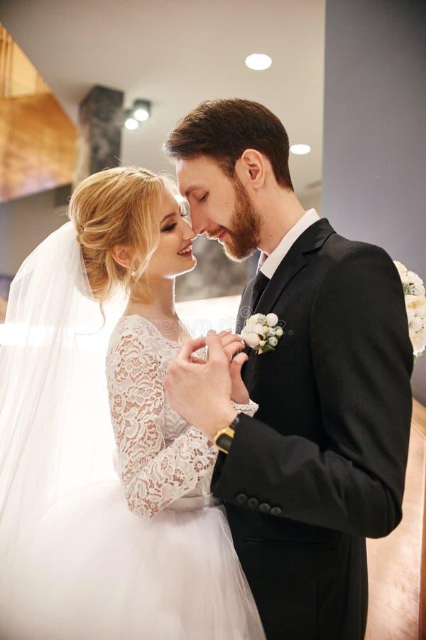 Bruid en bruidegom die en op hun huwelijksdag koesteren kussen Creati royalty-vrije stock foto
