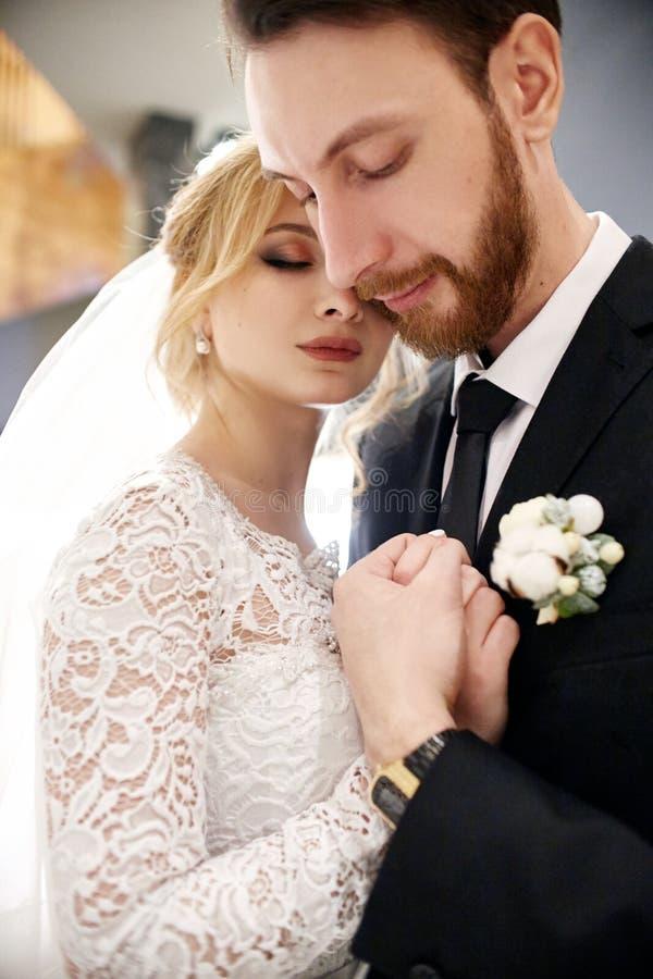 Bruid en bruidegom die en op hun huwelijksdag koesteren kussen Creati royalty-vrije stock afbeeldingen