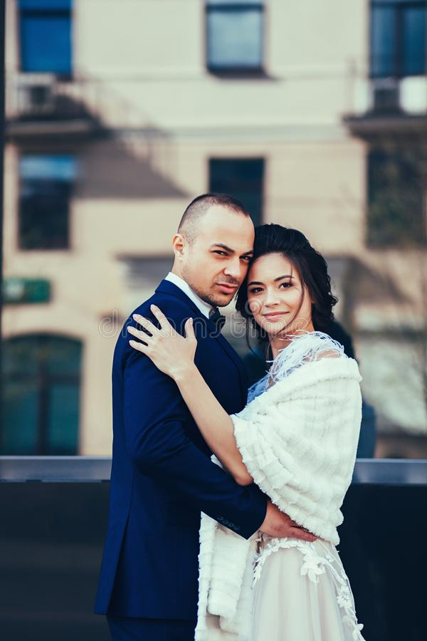 Bruid en bruidegom die in stad koesteren stock fotografie