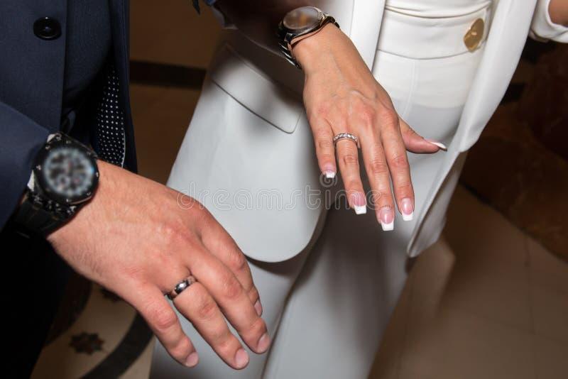 Bruid en bruidegom die trouwringen op hun vingers tonen Mannelijke en vrouwelijke handen met trouwringen stock afbeelding