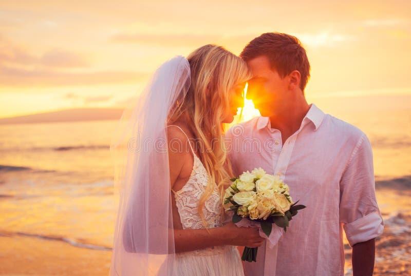 Bruid en Bruidegom, die Verbazend Zonsondergang op Mooie Tropisch genieten van royalty-vrije stock afbeeldingen