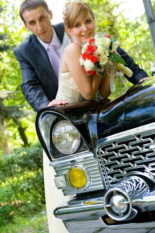 Bruid en bruidegom die zich dichtbij huwelijksauto bevinden royalty-vrije stock afbeelding