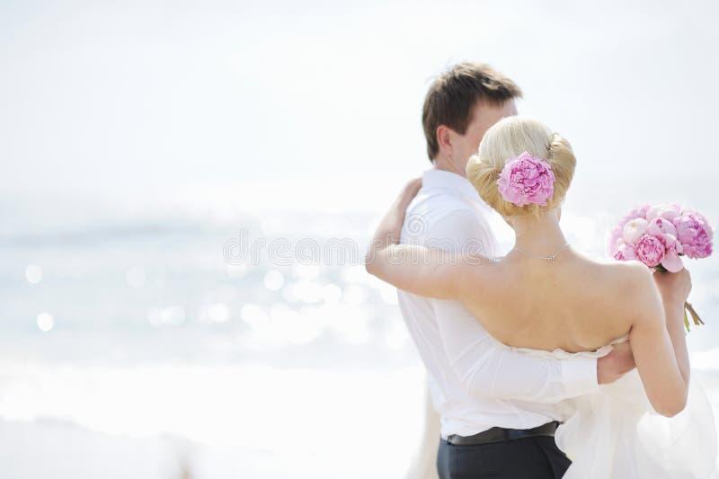 Bruid en bruidegom door het overzees stock foto's