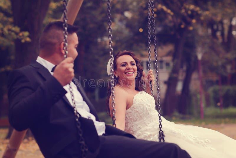 Bruid en bruidegom in een schommeling stock foto's