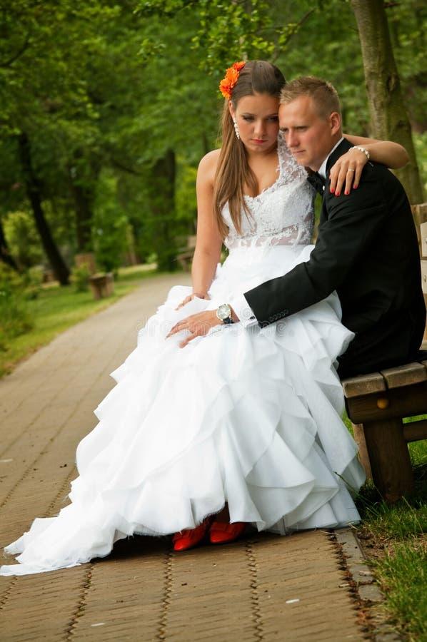 Bruid en bruidegom gezet in park royalty-vrije stock afbeelding