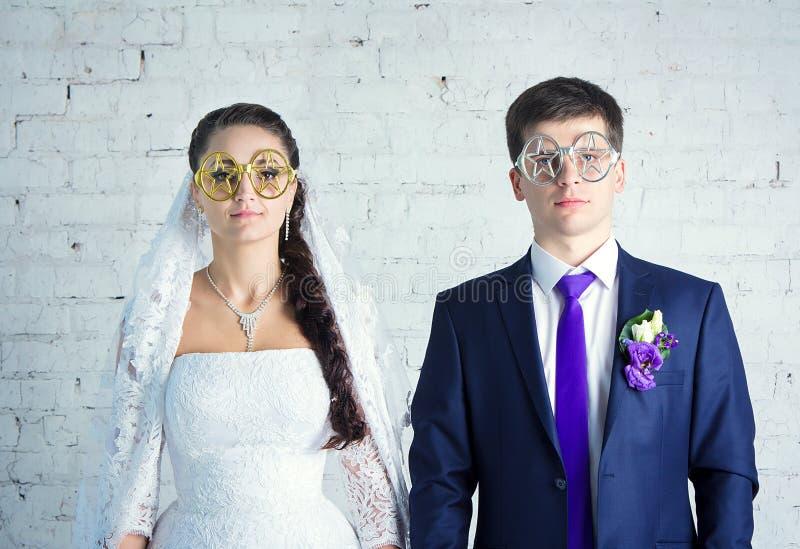Bruid en bruidegom in grappige glazen stock foto